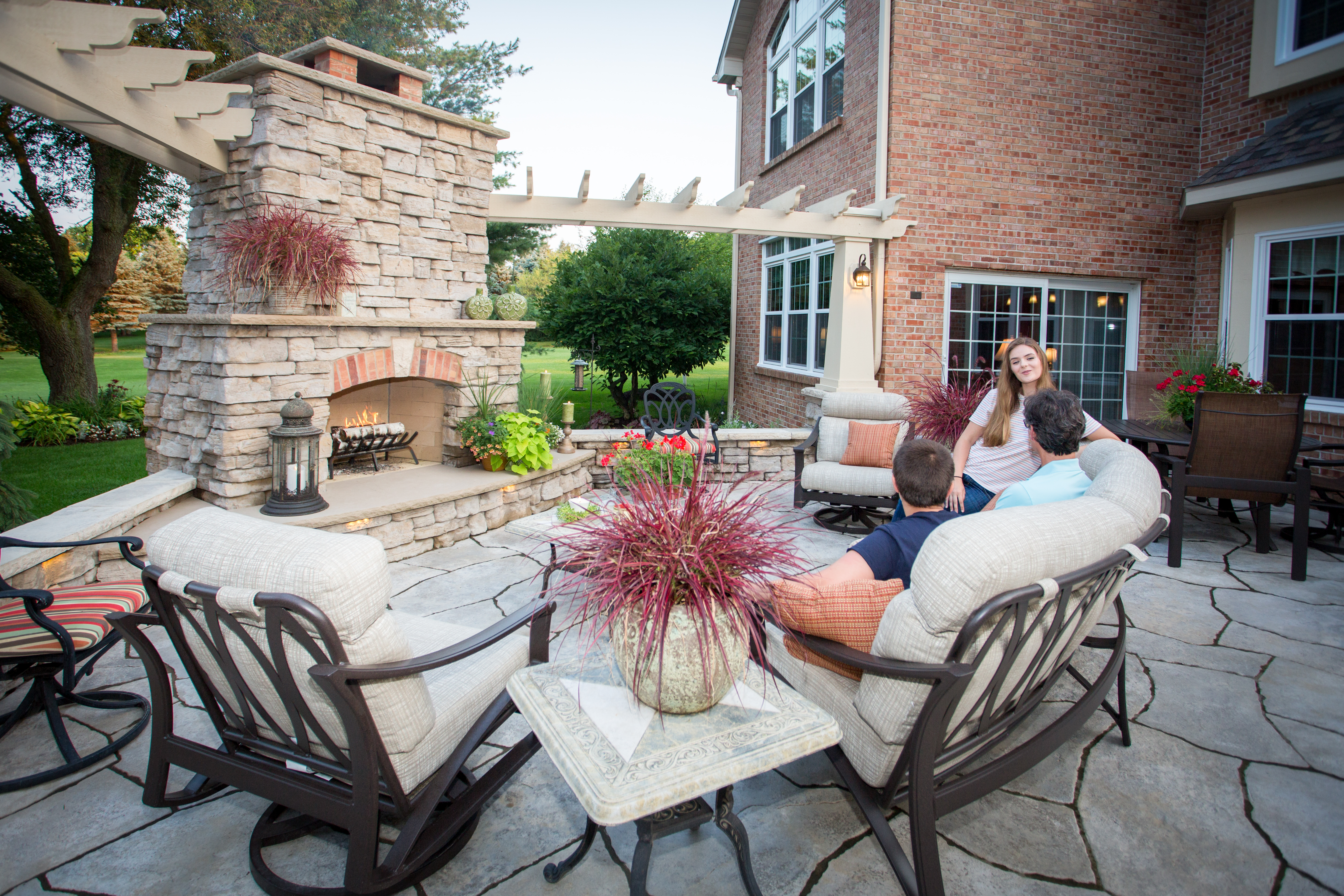 "Make ""family time"" synonymous with ""outdoor time"" with a Rosetta Fireplace. Products shown: Belvedere Fireplace Kit, Belvedere Walls, Dimensional Coping, and Grand Flagstone"